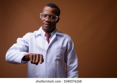 Studio shot of young African man doctor wearing protective glasses against brown background
