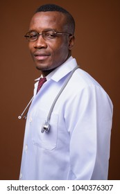 Studio shot of young African man doctor wearing eyeglasses against brown background