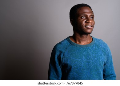 Studio shot of young African man wearing blue long sleeved shirt against gray background