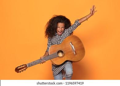 Studio shot of young  African teenage girl playing on guitar.
