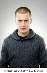 Studio shot of young angry man on gray background