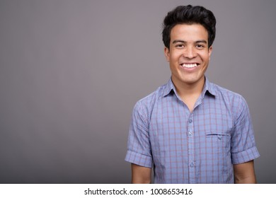 Studio shot of young Asian businessman against gray background