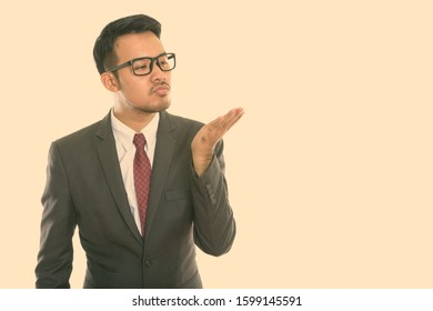 Studio shot of young Asian businessman giving flying kiss