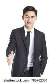 studio shot of a young asian businessman reaching out for a handshake, looking at camera smiling, isolated on white background.
