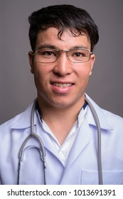 Studio shot of young Asian man doctor wearing eyeglasses against gray background
