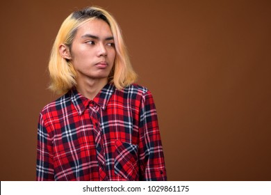Studio shot of young Asian man wearing stylish clothes against brown background