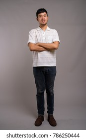 Studio shot of young Asian man wearing white striped polo shirt against gray background