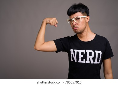14bc81bfbed5 Studio shot of young Asian nerd man wearing eyeglasses against gray  background