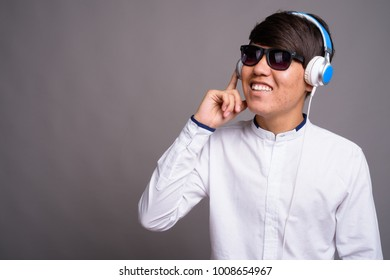 Studio shot of young Asian teenage boy listening to music against gray background