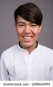 Studio shot of young Asian teenage boy wearing smart casual clothes against gray background