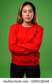 Studio shot of young Asian woman wearing red sweater against green background