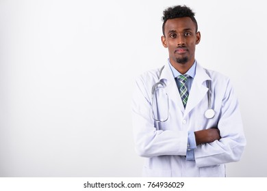 Studio shot of young bearded African man doctor against white background