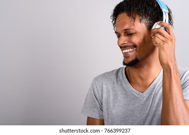 Studio shot of young bearded handsome African man listening to music against gray background