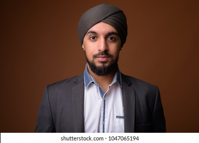 Studio shot of young bearded Indian Sikh businessman against brown background
