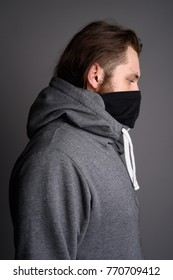 Studio shot of young bearded man wearing gray hoodie and mask against gray background