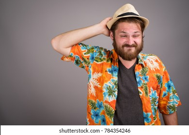 Studio shot of young bearded tourist man ready for vacation against gray background