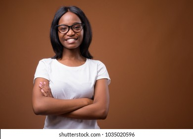 Studio shot of young beautiful African Zulu woman wearing white shirt against brown background