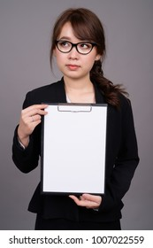 Studio shot of young beautiful Asian businesswoman wearing eyeglasses against gray background