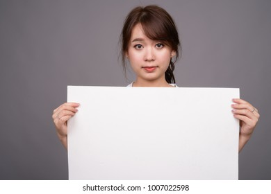 Studio shot of young beautiful Asian businesswoman holding white board against gray background
