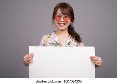Studio shot of young beautiful Asian tourist woman wearing Hawaiian shirt ready for vacation against gray background