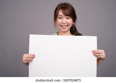 Studio shot of young beautiful Asian tourist woman wearing Hawaiian shirt ready for vacation against gray background