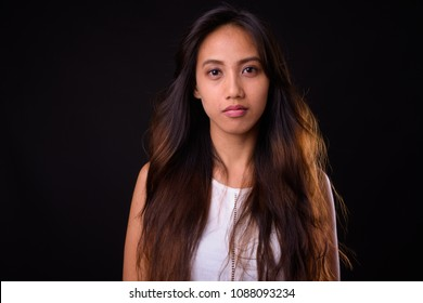 Studio shot of young beautiful Asian woman against black background