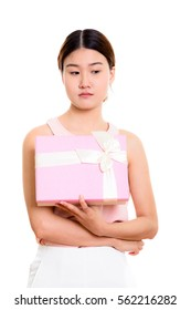 Studio shot of young beautiful Asian woman holding gift box while thinking