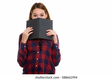 Studio shot of young beautiful Asian woman hiding behind book