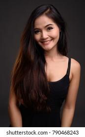 Studio shot of young beautiful Asian woman wearing black dress against gray background