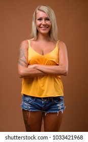 Studio shot of young beautiful blonde woman from Finland against brown background