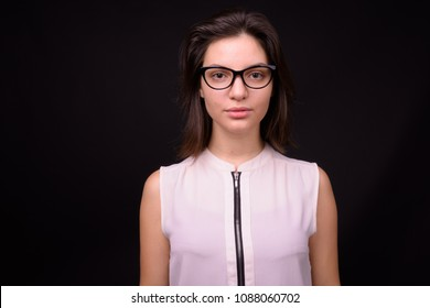 Studio shot of young beautiful businesswoman against black background