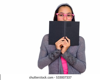 Studio shot of young beautiful Caucasian teenage girl hiding behind book isolated against white background
