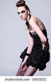Studio shot of a young, beautiful, fashion model with black make-up, dress and beads