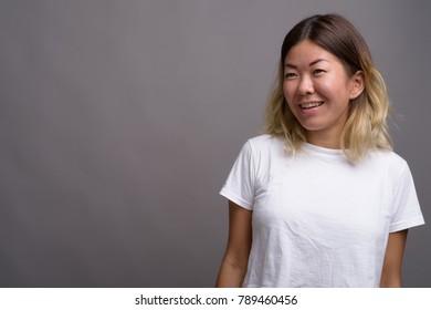 Studio shot of young beautiful Kazakh woman against gray background