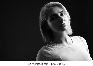 Studio shot of young beautiful rebel woman against black background in black and white