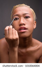 Studio shot of young beautiful rebellious Asian woman with short hair against gray background