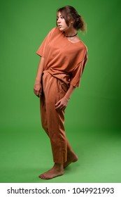 Studio shot of young beautiful woman wearing brown shirt and pants against green background