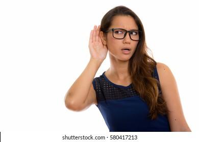 Studio shot of young beautiful woman listening