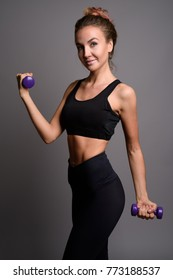 Studio shot of young beautiful woman ready for gym against gray background