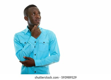 Studio shot of young black African man thinking while looking up