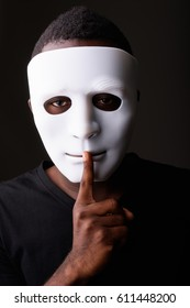 Studio shot of young black African man in dark room wearing mask and holding finger on lips