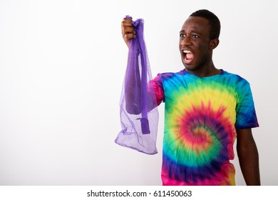 Studio shot of young black African man holding empty exercise mat net against white background