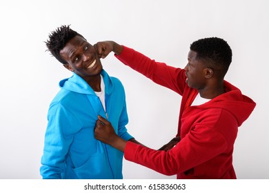 Studio shot of young black African man punching happy slim black African man smiling against white background