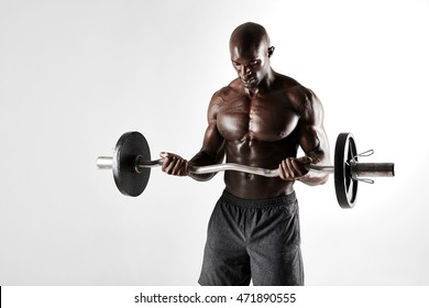 Studio shot of young bodybuilder training over grey background. Muscular african male model lifting barbell.