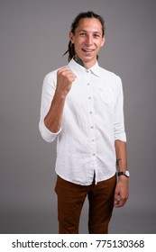 Studio shot of young businessman with dreadlocks against gray background