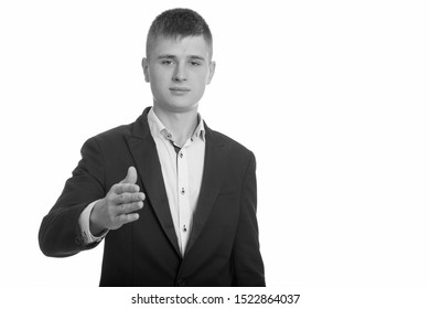 Studio shot of young businessman giving handshake