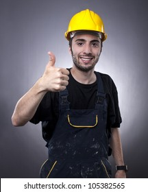 Studio shot of young construction worker with thumbs up