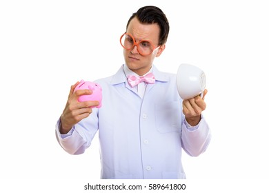Studio shot of young crazy man doctor looking at piggy bank while holding empty coffee cup