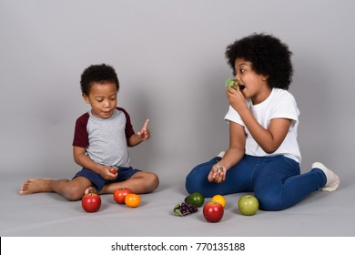 Studio shot of young cute African siblings together against gray background