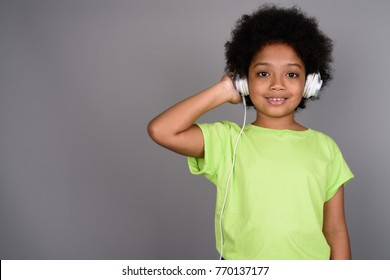Studio shot of young cute African girl listening to music against gray background